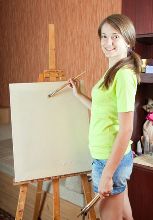 Pretty girl with brushes standing  near easel indoor   photo