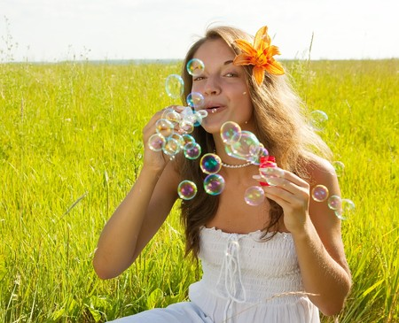 girl making soap bubbles on meadow grass