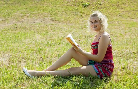 young beautiful woman reads on  green field in summer photo