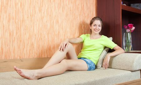 Smiling girl light clothing on beige couch photo