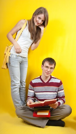 Two students with books  over a yellow background. photo
