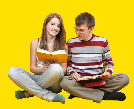 Young smiling students with books. Over yellow background photo