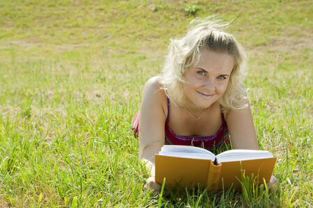 Young reading woman lying in grass during sunny day  photo