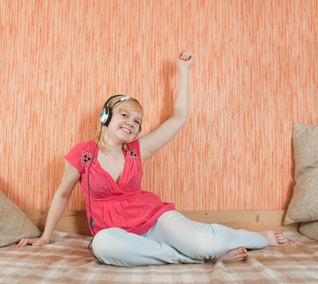 househould: Young   happy women listening music in headphones on  couch