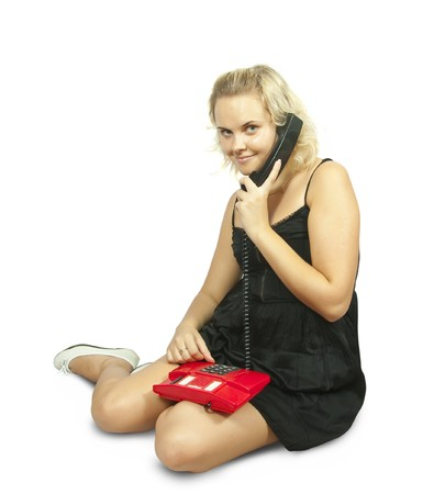 Happy young woman sitting and talking on phone photo