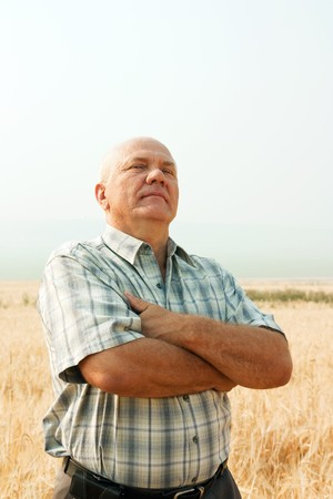 successful businessman standing outdoor on field of wheat photo