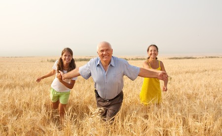 Beautiful cheerful family  runing over a field