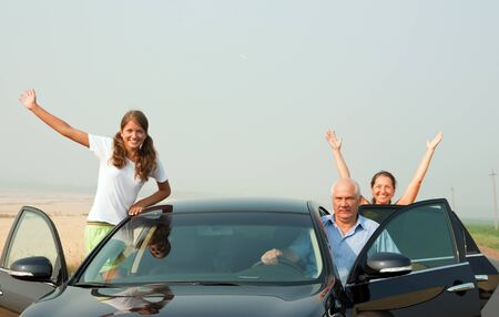 Beautiful cheerful family in the black car on summer countryside