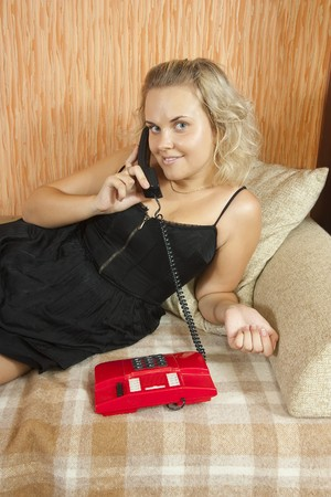 girl with red telephone lying on a sofa in the living-room photo