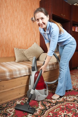 Photo of an attractive senior woman vacuuming her living room. Stock Photo