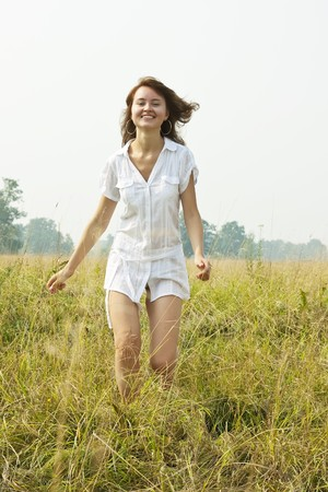 Brunette sexy girl running  in meadow grass photo