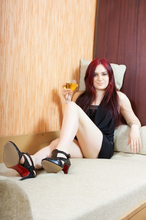 Luxury girl in little black dress with glass of wine photo