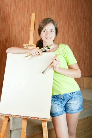 Pretty girl with brushes standing  near easel indoor Stock Photo - 7601771