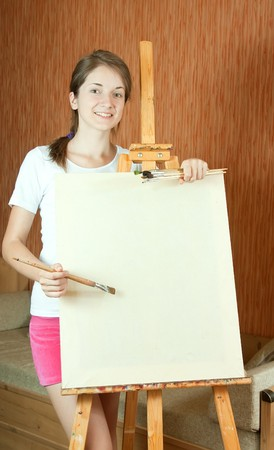 Pretty girl with brushes standing  near easel indoor Stock Photo - 7601777