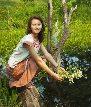 seamaid: girl in traditional clothes with flowers at river
