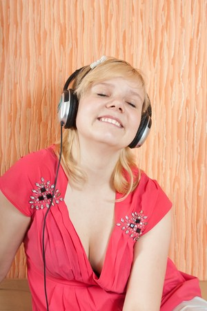 househould: Young beautiful happy women listening music in headphones on  couch