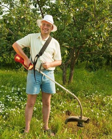 Smiling gardener is fixing lawn trimmer  in garden Stock Photo - 7629858