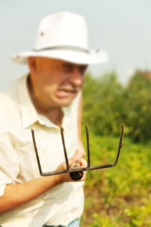 pitchfork: angry  farmer standing in farm field with a pitchfork. Focus on fork Stock Photo