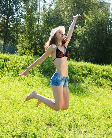 Jumping girl against summer meadow in summer day photo