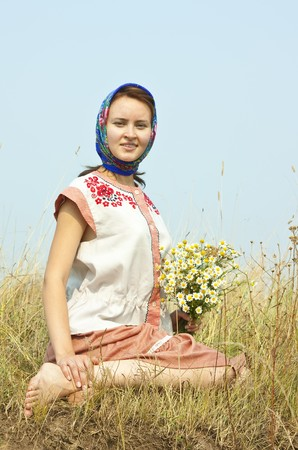 girl with flowers  in traditional clothes lying from meadow photo