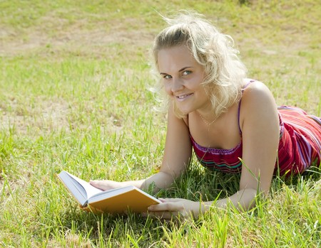 Blond girl on green field with yellow book photo