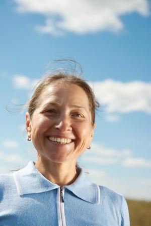 Portrait of mature woman against summer landscape Stock Photo
