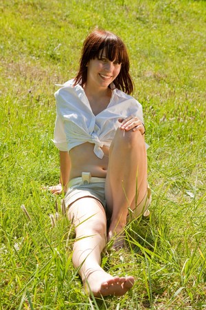 Pretty girl in shorts lying in meadow grass photo