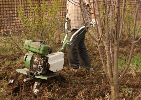 motor hoe: Close-up of man  plowing his spring yard with motor cultivator Stock Photo