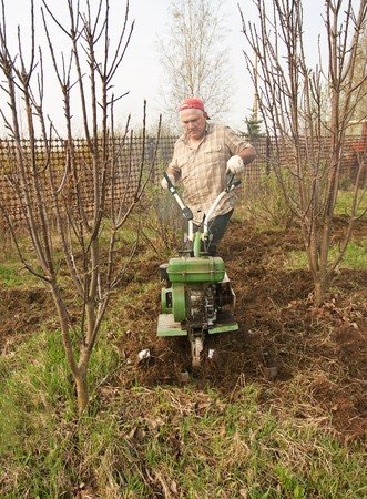motor hoe: working man with motor cultivator against spring time in garden Stock Photo