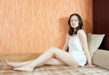Pretty  asian girl in short dress sitting on sofa at home photo
