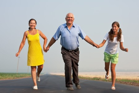Happy family of three run over a  road at summer photo