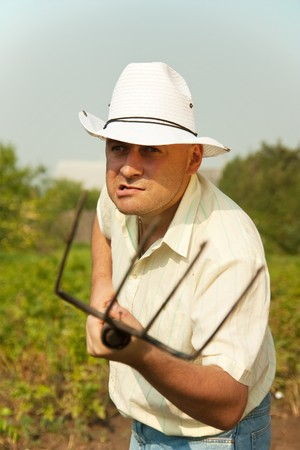 angry farmer standing in farm field with a pitchfork