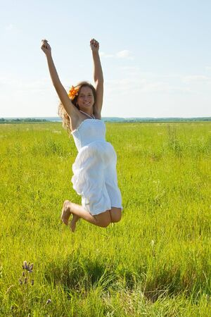 Jumping  pretty brunette  girl  against summer meadow Stock Photo - 7908124