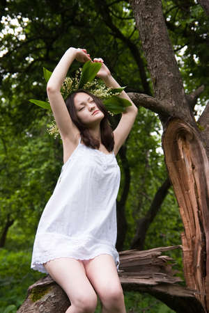 Beautiful Asian girl in white over forest photo
