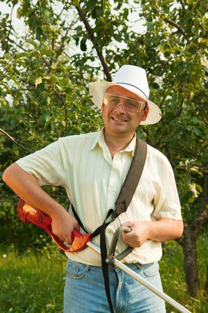 trimmer: A man works with cordless grass trimmer in garden Stock Photo