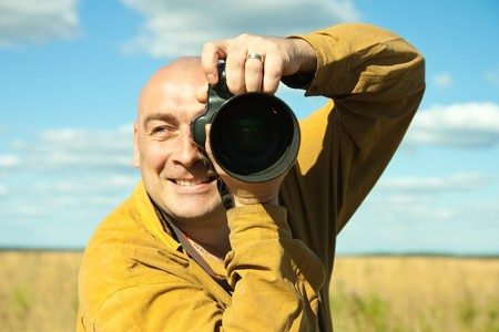 Adult man taking picture with digital camera over summer nature