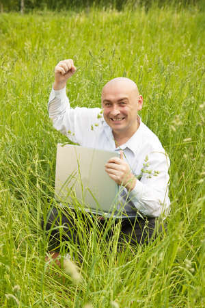 Young happy men working on laptop in the meadow photo