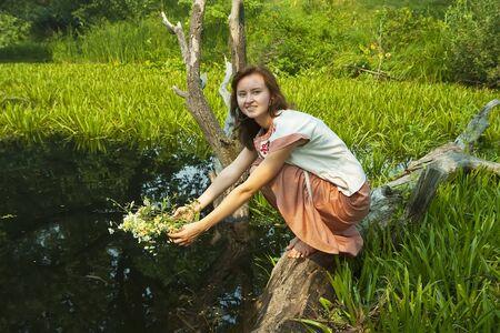 undine: Pretty girl  in flower chaplet at river Stock Photo