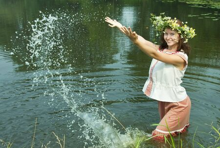 girl  in russian traditional clothes playing into water photo