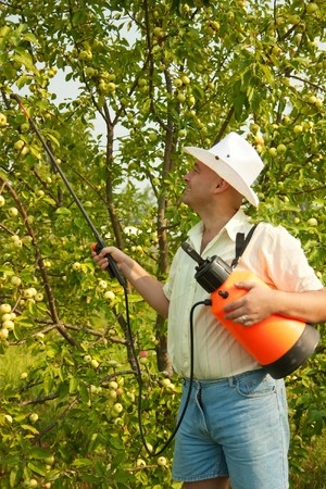 A man holding  garden spray and working in the yard photo