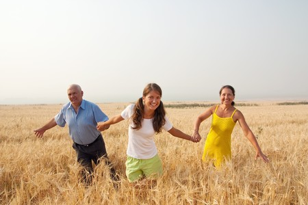 Beautiful cheerful family  go for a walk over a field  photo