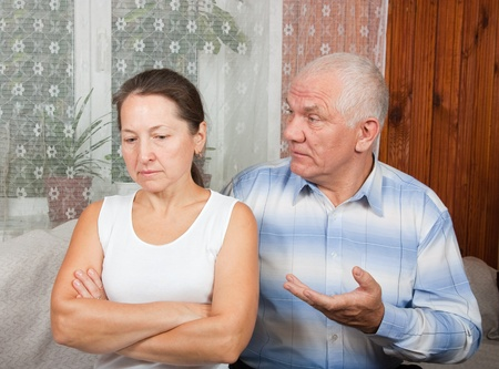 mature couple having a fight, at home on sofa