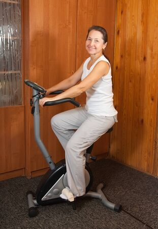 Mature woman working out on exercycle at home photo