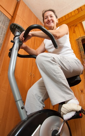 Senior woman on bicycle simulator in fitness center photo