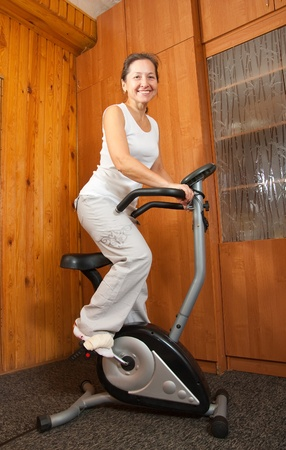 Mature woman in  sportswear exercising on exercise bike photo