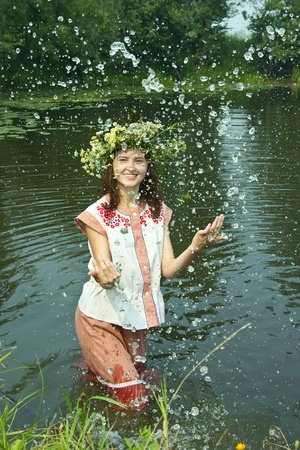 undine: girl  in russian traditional clothes playing into water Stock Photo