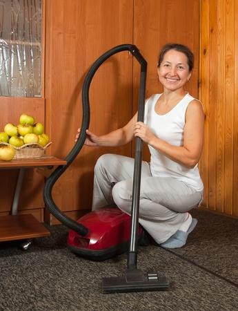 housekeeper. She is vacuuming the entry foyer into  home photo