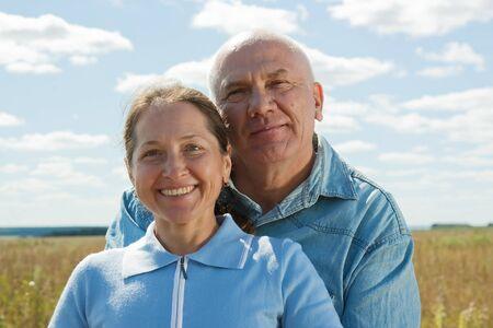 Lovely mature couple poising against summer landscape