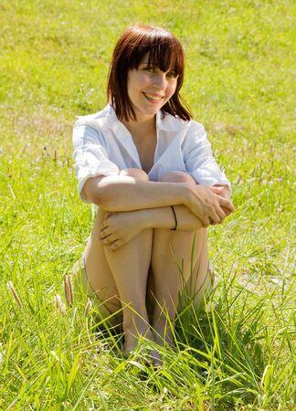 Pretty girl in shorts lying in meadow grass photo