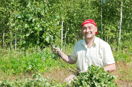 badhuis: man in a grove do birch besoms for a bath-house